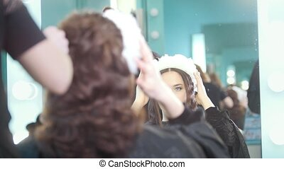 Hairdresser making curly hair for beautiful model, close up