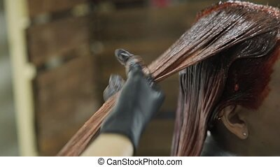hairdresser making hair coloring for young woman. beauty, hairstyle and people concept