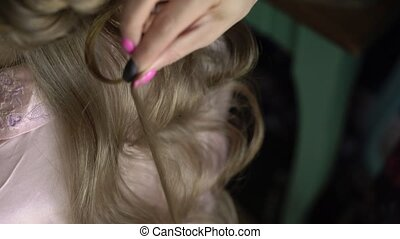 Hairdresser making hairstyle for woman