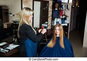 Hairdresser making hairstyle with scissors.