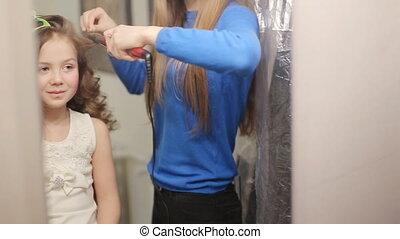 hairdresser perm hair of cute little girl