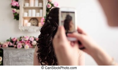hairdresser pictures of a wedding hairstyle on the phone in...