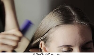 Hairdresser plaiting braids for young brunette woman.