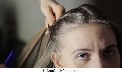 Hairdresser plaiting braids for young brunette woman