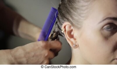 Hairdresser plaiting braids for young brunette woman....