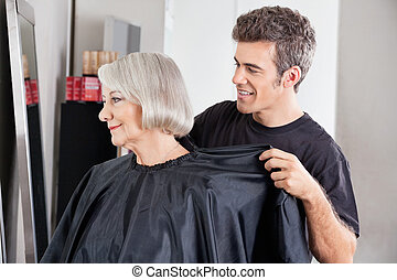Hairdresser Removing Client's Apron After Haircut