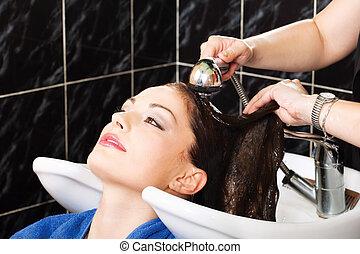 Hairdresser rinse customers hair