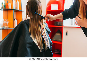 Hairdresser runs the comb, female client