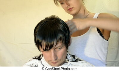 Hairdresser shears and combs her hair men