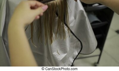 Hairdresser shortening hair tips with scissors - Hands of...