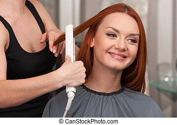 Hairdresser straightening long red hair with hair irons. Beautiful young lady straightening hair at hairdresser salon