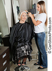 Hairdresser Straightening Woman's Hair At Parlor