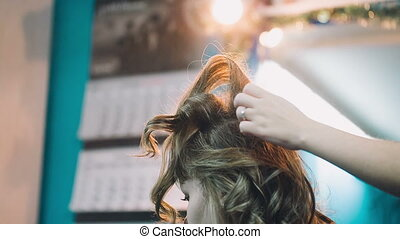 Hairdresser straightens client hair.