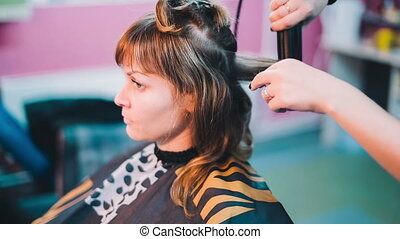 Hairdresser straightens the hair of the client.