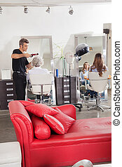 Hairdresser Styling Customer's Hair At Parlor