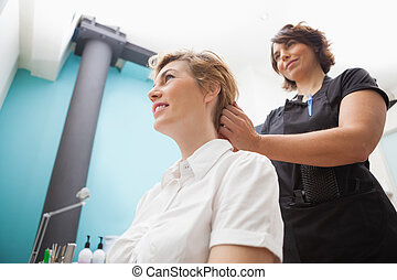 Hairdresser styling customers hair at work