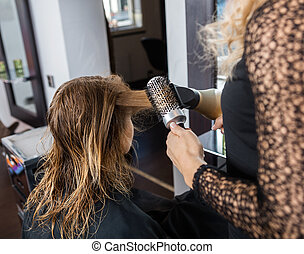 Hairdresser Styling Customer's Hair In Salon