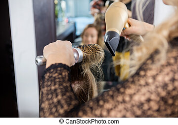 Hairdresser Styling Female Customer's Hair In Salon