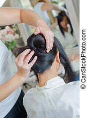 Hairdresser styling lady's hair