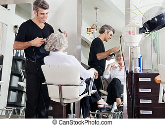 Hairdresser Styling Woman's Hair - Male hairdresser styling...