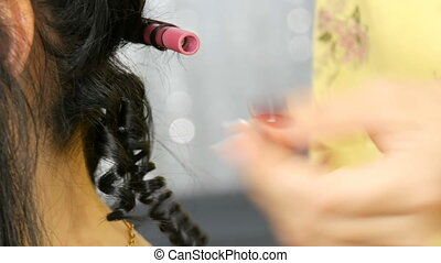 Hairdresser stylist makes a special curl small curly hair with a special curling iron