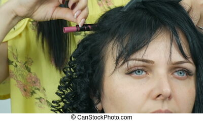 Hairdresser stylist makes a special curl small curly hair...