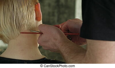 Hairdresser trimming blond hair with scissors.