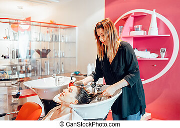 Hairdresser washes hair in hairdressing salon