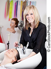 Hairdresser washing a clients hair in the salon -...