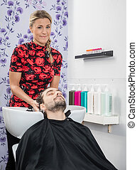 Hairdresser Washing Customer's Hair In Salon