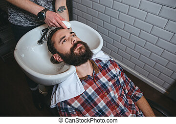 Hairdresser washing hair of young man with beard