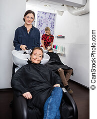 Hairdresser Washing Woman's Hair In Salon