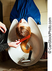 Hairdresser washing young woman's hair in salon.