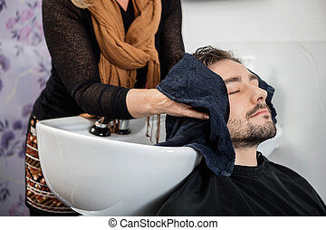 Hairdresser Wiping Male Client's Hair In Salon