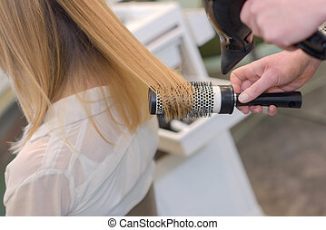 hairdresser with brush behind young female