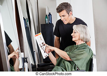 Hairdresser With Customer Selecting Color From Catalog