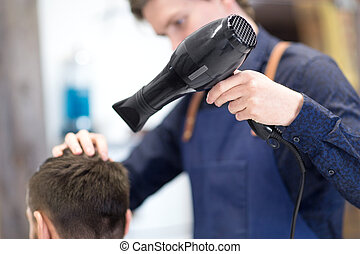 hairdresser with hair dryer drying male head - grooming, ...