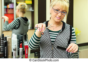 Hairdresser with scissors and comb in workplace near mirror in beauty salon