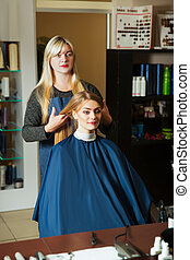 Hairdresser with woman in front of the mirror.
