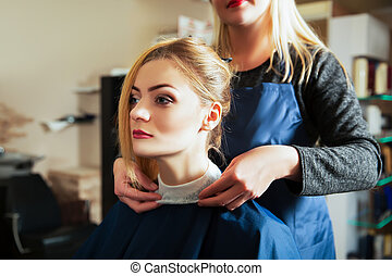 Hairdresser with woman in hairdressing salon.