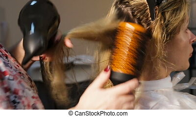 Hairdresser woman dries the hair dryer - Beautiful woman at...