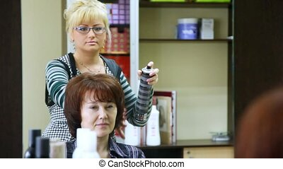 Hairdresser-woman in end of session hairdress fasten her by hairspray