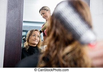 Hairdresser Working On Client's Hair In Salon
