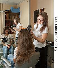 hairdresser working with hair dryer