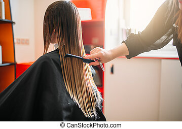 Hairdresser works with spray, female hairdressing