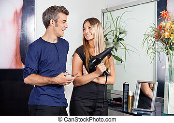 Hairdressers Looking At Each Other In Salon