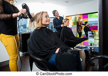 Hairdressers Setting Client's Hair In Salon