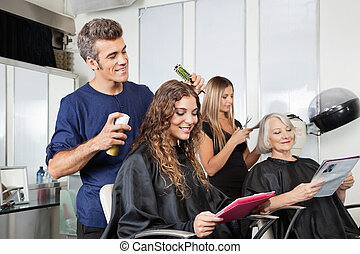 Hairdressers Setting Up Client's Hair In Salon - Male and...
