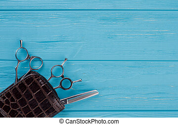 Hairdressing scissors on blue wooden background.