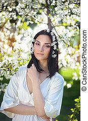 haired, mujer, en, un, primavera, parque, con, flores, en, ella, pelo